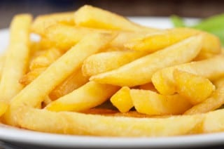 Golden potatoes fries in the plate closeup